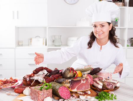 Young brunette girl shows a sausages and smoked products which lie on table