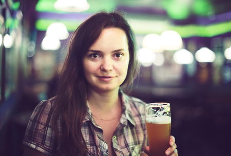 Portrait of young sexy girl sits in bar with beer glass