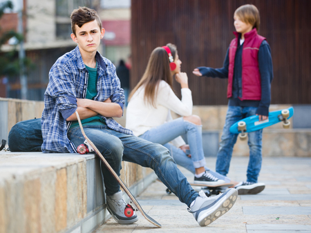 16s: Jealous european teen and his friends after conflict outdoors Stock Photo