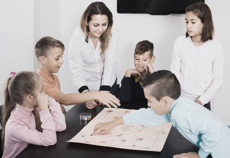 next year: smiling russian children making move on pre-marked surface of board game at classroom