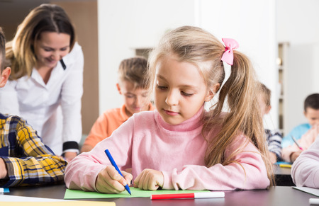 Female teacher and elementary age children drawing at classroom