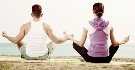 Glad cheerful  woman and man sitting cross-legged do yoga poses on beach at daytime Stock Photo
