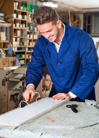 Smiling working man practising his skills in plank chiseling at workshop Stock Photo