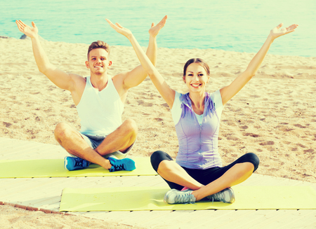 Cross-legged russian positive couple practice yoga on beach in morning Stock Photo