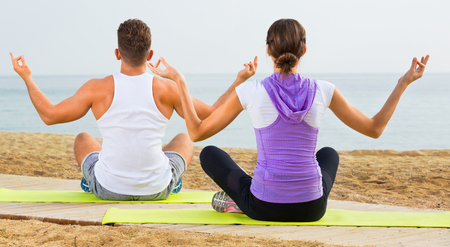 Happy friendly woman and man sitting cross-legged do yoga poses on beach at daytime
