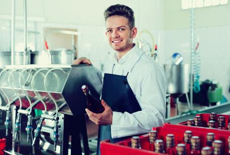 Diligent  smiling male worker packaging wine bottles at sparkling wine factory