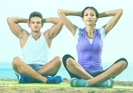 Cheerful woman and man sitting cross-legged do yoga poses on beach at daytime Stock Photo