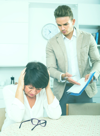 Brunette woman has discontentedly turned away from man who suggests her to sign documents