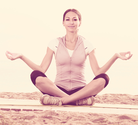 Smiling woman practise yoga cross-legged in morning by sea Stock Photo