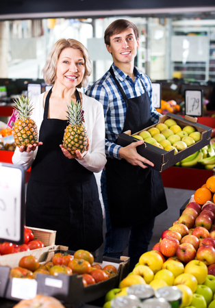 Portrait of cheerful senior woman and young man offering seasonal fruits. Focus on the woman Stock Photo