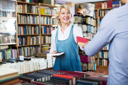 Adult woman taking book in book shop and talking to seller Stock Photo