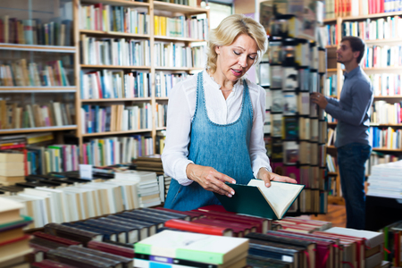 Woman reading book while choosing it in book shop Stock Photo