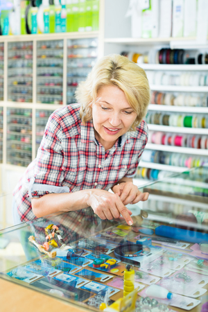 Portrait of mature cheerful woman standing next to glass showcases in the shop with sewing goods