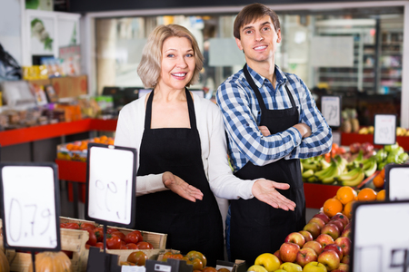 friendly sellers posing with fruits in local supermarket Stock Photo