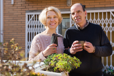 Elderly positive female talking with male neighbor at balcon Stock Photo