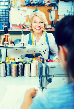 professional mature woman tailor using sewing machine at workshop Stock Photo