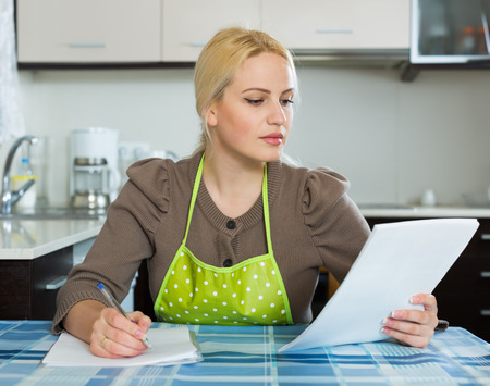 Serious woman filling in the financial documents at table in home kitchen