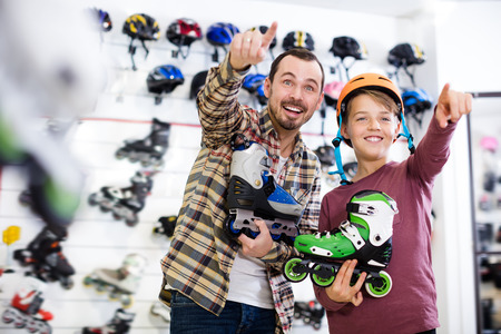 boasting: Happy father and boy boasting purchased roller-skates in sports store Stock Photo