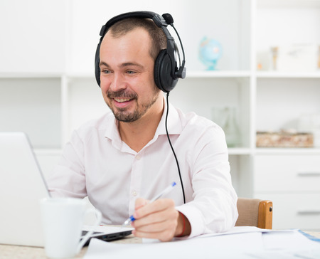 Positive young man sitting in headphones at his computer