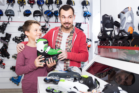adult russian father and son deciding on new roller-skates in sports store Stock Photo