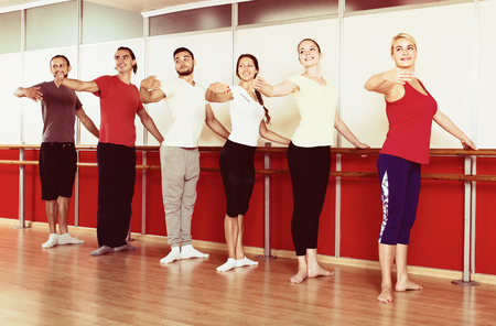 Group of smiling spanish men and women practicing at the ballet barre