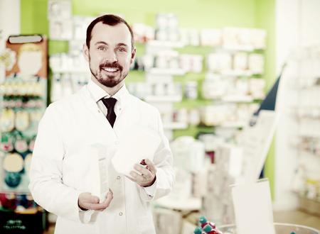Smiling man pharmacist offering assortment in pharmacy