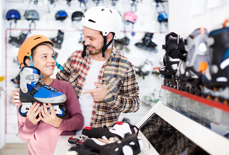 smiling american father and son deciding on new roller-skates in sports store