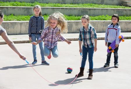 肯定的な女の子屋外友達と縄跳びゲームしながらジャンプ 写真素材