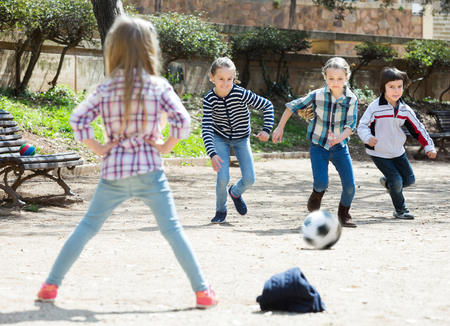 Portrait of active junior school girls and boy playing street football