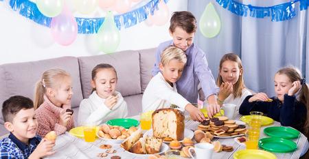 animation teenagers: Smiling children having dinner to celebrate friend's birthday