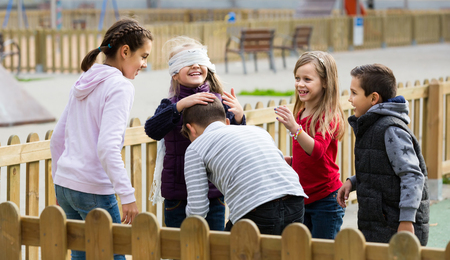 romp: positive european  kids playing at Dead man in street Stock Photo