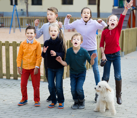 Group of smiling kids in high spirits jumping outdoors Stock Photo