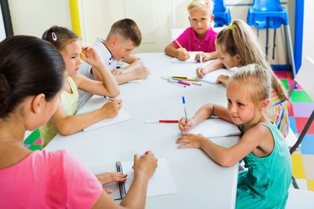 Happy kids writing together with tutor at school class indoors