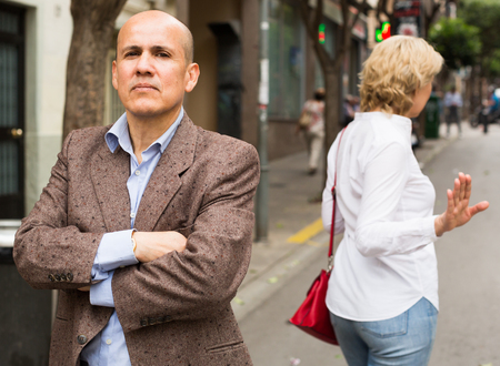 argumentation: closeup of angry retiree man being sad with woman standing outdoors Stock Photo
