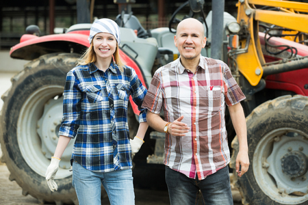 Senior and young farmers working at agricultural machinery in farm