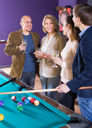 Group of cheerful different age friends with wine chatting near billiard table