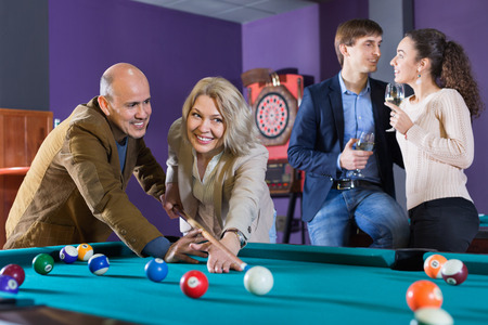Group of cheerful charming positive friends playing billiards and smiling in night club
