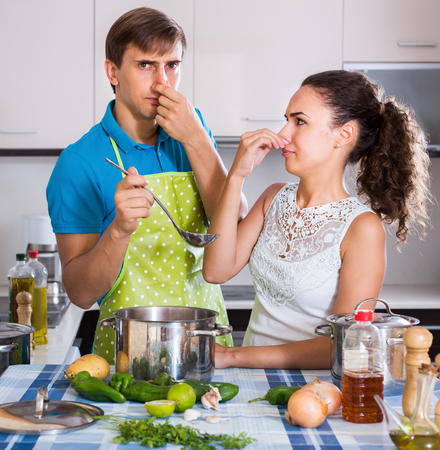 domestic kitchen: Husband and wife with stinking meal in domestic kitchen