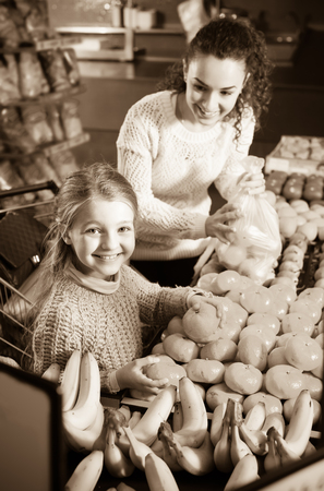 purchasers: Smiling young woman and little girl purchasing sweet tangerines at market
