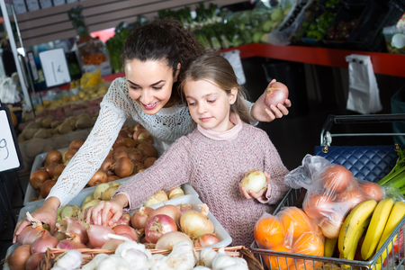 purchasers: Joyful young woman with cute little daughter selecting vegetables in grocery food store