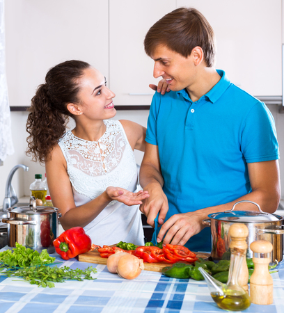 domestic kitchen: Happy young family couple cooking vegetables in domestic kitchen
