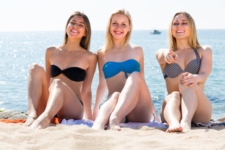 three young women friends in bikini sitting on sandy beach on sunny day
