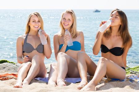 Three young smiling girls wearing swimwear sitting on beach and drinking water Stock Photo