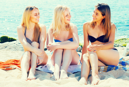 sunbath: three joyful  smiling girls in bikini relaxing on sandy beach on sunny day