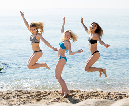 three young cheerful women friends looking happy in bikini and jumping on sandy beach. Selective focus