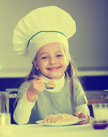 kasha: Little girl in cook hat with milk and oatmil kasha Stock Photo
