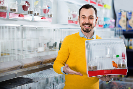 Young cheerful positive male customer boasting his purchase of canary bird in pet shop