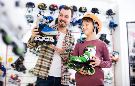 boasting: Man and son boasting purchased roller-skates in sports store Stock Photo
