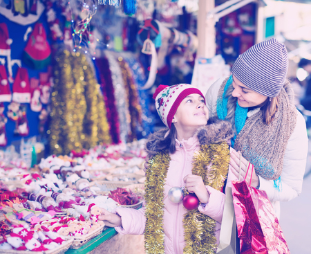 overspending: Happy mother with joyous little daughter buying decorations for Xmas at an open air market