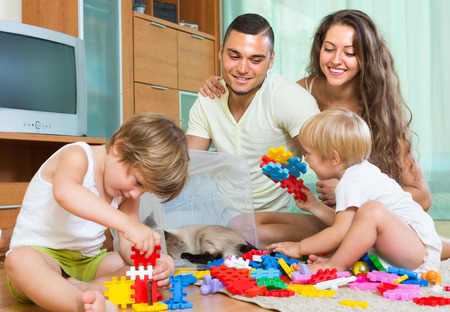 Happy man with young wife and two daughters plays with meccano set in home